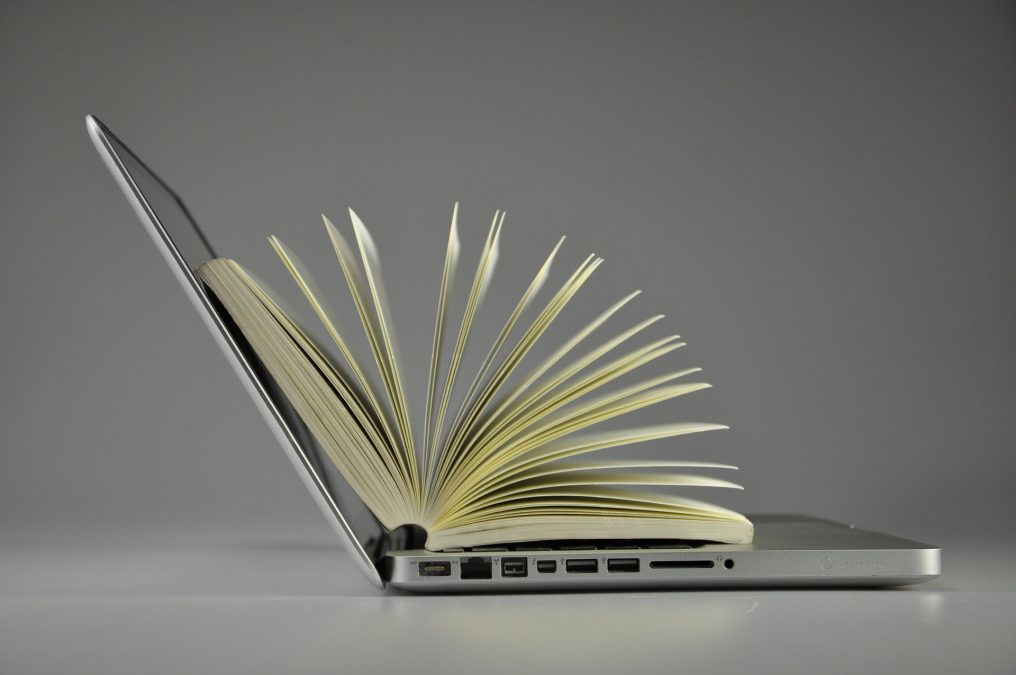 offenens Buch auf offenem Laptop
